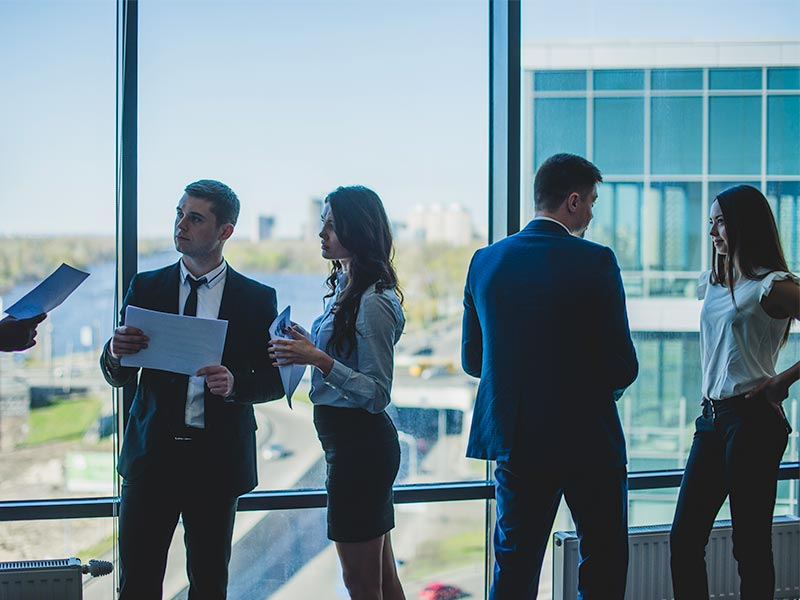 Group of business people chatting in front of a window.