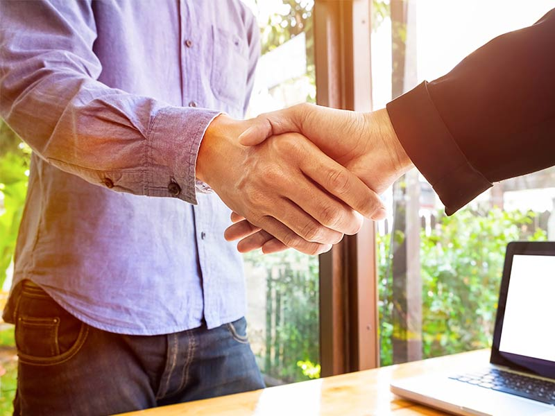 Casually dressed business man shaking hands with a colleague.