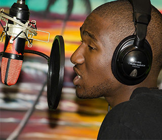 Man speaking in to microphone in recording studio