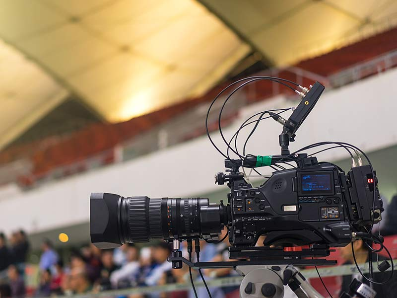 Video camera filming at large sports events.