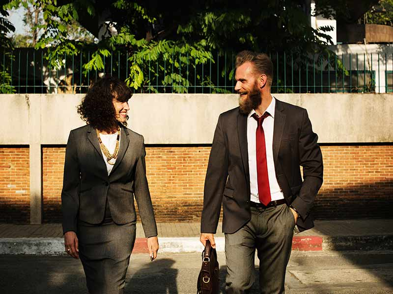 man and women wearing suits walking together