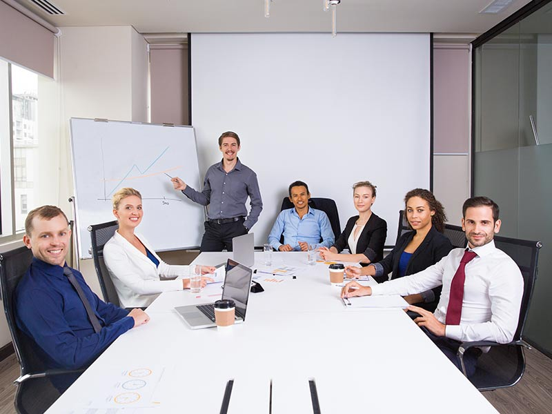 picture of business meeting with workers looking towards camera