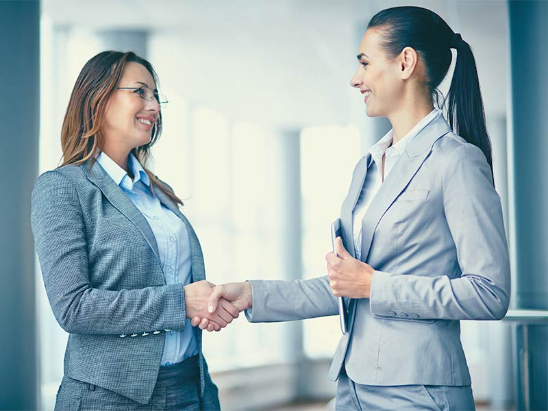 A businesswoman greeting a new colleague.